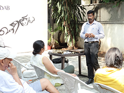 Suresh explaining the process of dhokra art to an interested audience