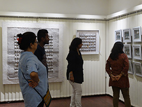 Visitors admire the intricacy of the work