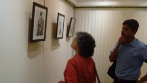 People look on at Pooja Kamble's work.