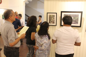 Visitors look at the photographs.